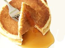Pancakes. Image of two sliced pancakes and metal fork, with a stream of maple syrup running off slices onto plate Stock Images