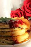 Pancakes. Appetizing pear fritters decorated with raspberry jam and a sprig of mint on a white background with roses Royalty Free Stock Photography