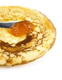 Pancakes. Applying apricot marmalade on a pancake royalty free stock photo
