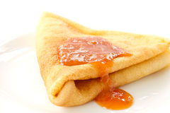 Pancakes with apricot jam. Sweet pancakes with apricot jam on a white plate Royalty Free Stock Photo