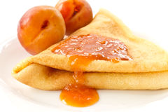 Pancakes with apricot jam. Sweet pancakes with apricot jam on a white plate Royalty Free Stock Photography