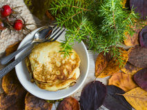 Pancakes and autumn leaves. Pancakes with autumn leaves and branches of larch decorated on a wooden table royalty free stock photos