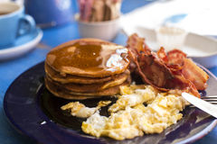 Pancakes, bacon and eggs with dripping maple syrup on a breakfast plate on a table Royalty Free Stock Images