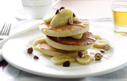 Pancakes with banana. A stack of pancakes with banana slices, toasted hazelnuts, and maple syrup Royalty Free Stock Photos