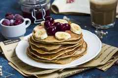Pancakes with banana and berries stock photography