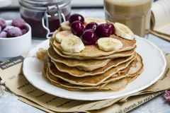 Pancakes with banana and cherries stock images