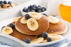 Pancakes with banana, honey and blueberries for breakfast Royalty Free Stock Photos