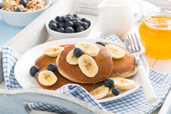 Pancakes with banana, honey and blueberries for breakfast Royalty Free Stock Images