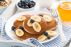 Pancakes with banana, honey and blueberries for breakfast. On a tray, horizontal stock photography