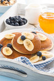 Pancakes with banana, honey and blueberries for breakfast Royalty Free Stock Image