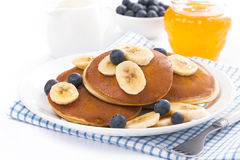 Pancakes with banana, honey and blueberries, isolated Stock Image