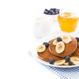 Pancakes with banana, honey, blueberries and yogurt, isolated Stock Image