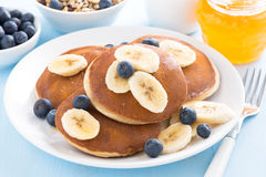 Pancakes with banana, honey and blueberry on a plate Royalty Free Stock Photography