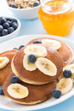 Pancakes with banana, honey and blueberry, vertical Stock Images