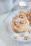 Pancakes with banana and sugar powder. Homemade pancakes with sugar powder and flower-shaped banana slices on light blue plate. Selective focus Royalty Free Stock Photo