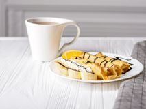Pancakes with banana, whipped cream decorated with chocolate syrup on white wooden background and cup of tea. Pancakes with banana, whipped cream and chocolate royalty free stock images