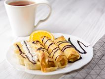 Pancakes with banana, whipped cream decorated with chocolate syrup on white wooden background. And a cup of tea. Pancakes with banana, whipped cream and stock images