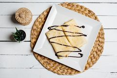 Pancakes with banana, whipped cream and chocolate syrup on white wooden background. Pancakes with banana, whipped cream and chocolate syrup on the white wooden stock image