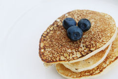 Pancakes with berries. Russian thick pancakes on a white plate close-up with fresh blueberries Royalty Free Stock Photo