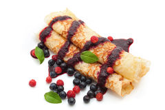 Pancakes with berries. Pancakes rolled in a tube with berries, filled with berry sauce on a white background Royalty Free Stock Photography