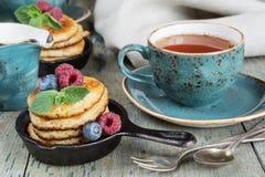 Pancakes with berries. Breakfast of pancakes, fresh berries and black tea in blue ceramic cup in rustic style Stock Photo