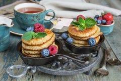Pancakes with berries. Breakfast of pancakes, fresh raspberries, blueberries and black tea in blue ceramic vintage cup, in rustic style Royalty Free Stock Photo