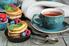 Pancakes with berries. Breakfast of pancakes, fresh raspberries, blueberries and black tea in blue ceramic vintage cup, in rustic style Royalty Free Stock Images