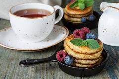Pancakes with berries. Breakfast of pancakes in a portioned cast-iron frying pan, fresh berries and black tea in a vintage ceramic cup on an old wooden table Royalty Free Stock Photo