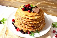 Pancakes with berries and chocolate. Sweet tasty pancakes with berrie fruits, chocolate and mint leaves stock photos