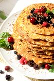 Pancakes with berries and chocolate. Sweet tasty pancakes with berrie fruits, chocolate and mint leaves royalty free stock photo