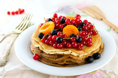 Pancakes with berries and fruits: apricot, red, blackcurrant. Pancakes with berries and fruits. Crepes stack with apricot, red and blackcurrant stock photos