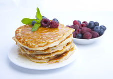 Pancakes with berries, honey and mint. Five pancakes with raspberries, blueberries, honey and mint on white background, food Stock Photography