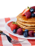 Pancakes with berries and honey over white Royalty Free Stock Photo