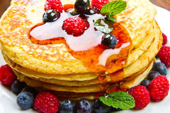 Pancakes with berries and maple syrup. Some Pancakes with berries and maple syrup Royalty Free Stock Photos