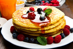 Pancakes with berries and maple syrup Stock Photography