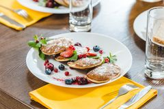 Pancakes with berries and mint on white plates. On wooden table stock photography