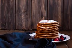 Pancakes and berries sprinkled with sugar stock image