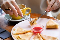 Pancakes with berry jam on a white plate on a wooden background close-up. Fork and knife in the hands of a woman. Next is a mug of. Cappuccino. Girl eating royalty free stock image