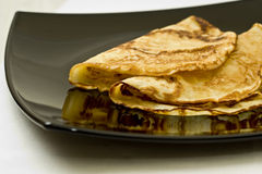 Pancakes on black plate. Tasty pancakes on a black plate. isolated on white stock images