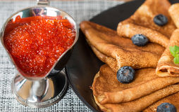 Pancakes on black plate with blueberry and red  caviar Stock Image