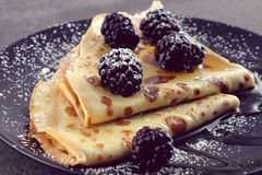Pancakes with blackberries and honey on a black plate. Pancakes with blackberries and honey and powdered sugar on a black plate on dark background Royalty Free Stock Photos