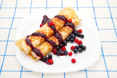 Pancakes with blueberries. Thin crispy fried pancakes with berry sauce, blueberries and strawberries Royalty Free Stock Image