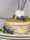 Pancakes with Blueberries. A stack of pancakes sitting on a white plate with fresh blueberries while being topped with whipped cream stock image