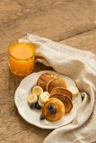 Pancakes with blueberries, banana and fresh orange juice royalty free stock photography