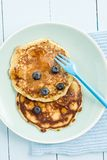 Pancakes with blueberries. On a blue plate stock photo