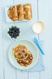 Pancakes with blueberries. And milk on blue background stock image