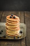 Pancakes. With blueberries piled up on dark wooden background stock photo
