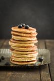 Pancakes. With blueberries piled up on dark wooden background stock photography