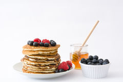 Pancakes with blueberries and raspberry isolated on white background Royalty Free Stock Photos