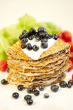 Pancakes with blueberries. Russian stack of pancakes filled with sour cream and fresh blueberries Royalty Free Stock Images